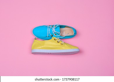 Female shoes bright blue and yellow colors. Top view flat lay design concept. Woman footwear on pink background.