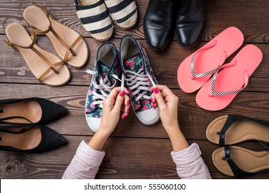 Female shoes collection on wooden table with woman's hands tying shoelace