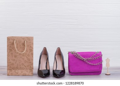 Female shoes, handbag and shopping bag. Black leather heels, pink clutch and kraft paper bag on wooden background. Purchases and shopping concept.