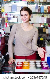 Female shop assistant is displaying assortment in cosmetics shop.