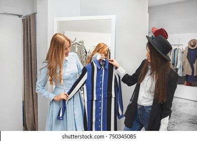 Female shop assistant helping her customer choosing a new dress. Young woman buying clothes at the local shopping mall service customer client friendly helpful profession occupation assistance.