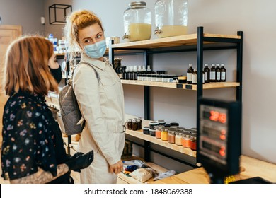Eine Ladenassistentin, die blond-geschweifte Kunden anbietet, trägt eine Schutzmaske in einer Mülltonne. Nachhaltiges Einkaufen in kleinen lokalen Unternehmen. Sicherheit in der Öffentlichkeit während der Covid-19-Epidemie.