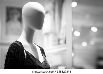 Female shop dummy fashion mannequin in department store boutique window wearing current women's fashions in clothes.