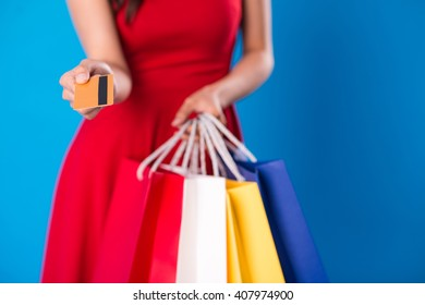 Female shopaholic giving you credit card, selective focus