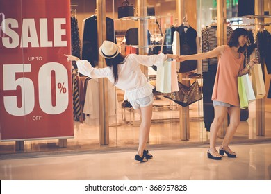 Female shopaholics going by the shop with big sale