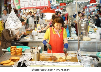 Female shopkeeper is cooking Bindaetteok (Mung bean pancakes) at Gwangjang Market that is one of the oldest traditional markets in Seoul, Korea on 21 September 2017