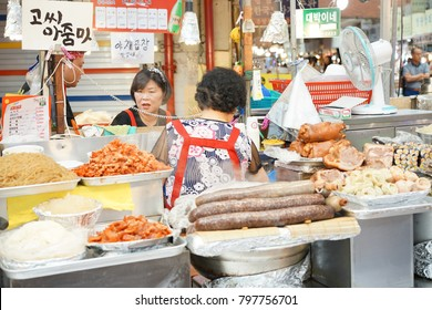 Female shopkeepers are cooking local food at Gwangjang Market that is one of the oldest traditional markets in Seoul, Korea on 21 September 2017