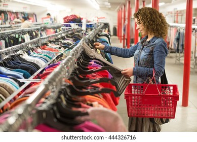 Female shopper browsing through clothing In a Thrift Store
