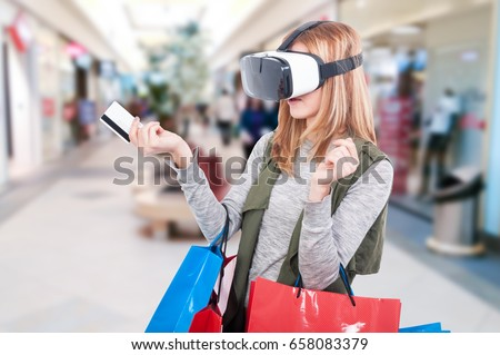 Female shopper experiencing virtual reality equipment video and using credit card as e-commerce shopping concept