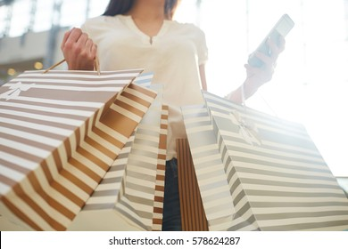 Female shopper with striped paper-bags