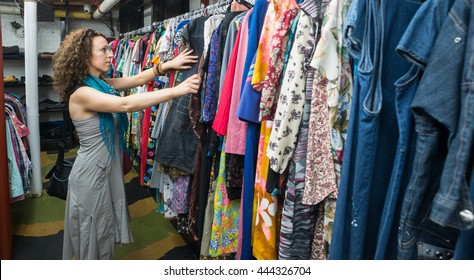 Female Shopper In Thrift Store browsing through vintage dresses
