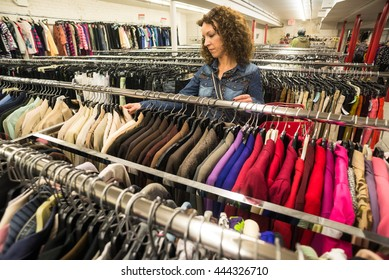 Female Shopper In Thrift Store browsing through coats