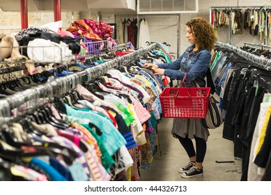 Female Shopper In Thrift Store browsing through clothing