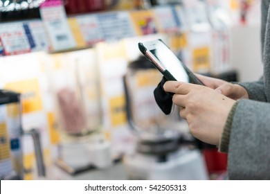 Female shopper using mobile phone during shopping