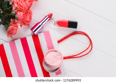 Female shopping accessories flat lay. White wooden background. Rose flowers, lipstic, mascara, powder and shopping bag.