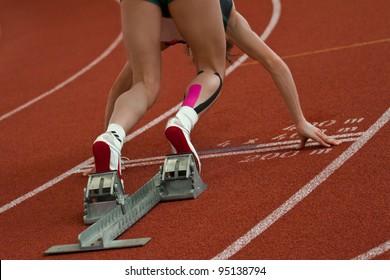 Female short distance runner  is in start position