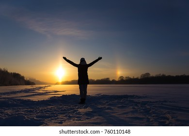 female silhouette against the background of the setting sun and the natural atmospheric phenomenon of parhelion or the false sun.