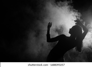 Female silhouette dancing in shadow and smoke