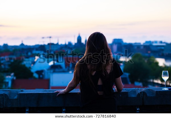 Female silhouette looking out over beautiful city sunset at night