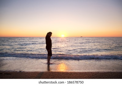 Female silhouette on seacoast against the sunset sky