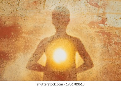 Female silhouette radiating light from within a spiritual heart opening.