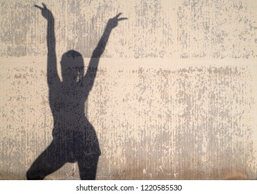 Female silhouette with raised arms showing both peace signs over worn-out background.