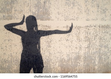Female silhouette of shadow against concrete wall in sunlight dancing expressively