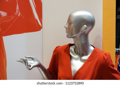 The female silver mannequin in profile without hair in a v neckline red dress with one hand at her chest level and visible collarbones on white red yellow black background