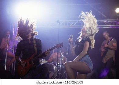Female singer and male guitarist with tousled hair performing together on stage at nightclub