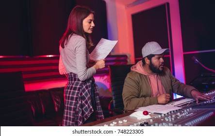 Female singer with man working on audio mixing console in recording studio. People working in professional music studio.