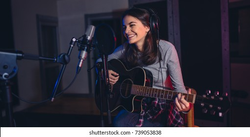 Female singer playing guitar and singing a song. Woman performing in a recording studio. Recording for her album.