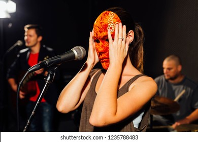Female singer is putting the mask on her face during the rehearsals. Drummer and guitarist in the blurry background.