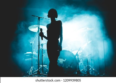 Female singer silhouette in front of a smoky stage