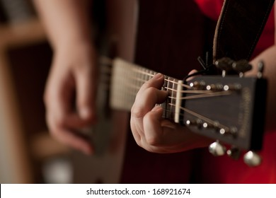 Female singer-songwriter playing an acoustic guitar