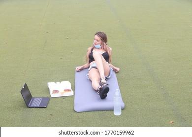 female sitting back on a yoga mat in the park enjoying a break