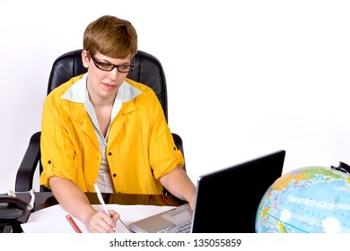 Female sitting behind a desk in bright, yellow jacket working on a laptop computer.
