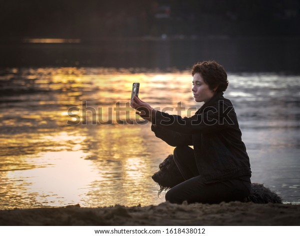 Female sitting by the lake with her dog taking a selfie with her phone camera.
