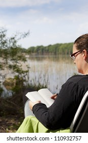 Female sitting in a chair reading a book with a lake in front of her. A boat is sailing on the lake. Focus is on the boat.