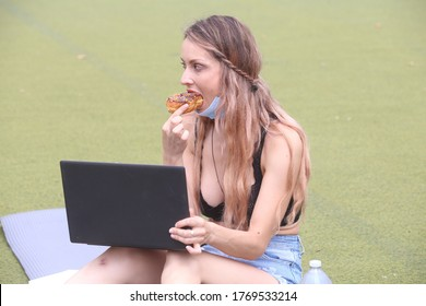 female sitting down outside eating a doughnut while working on a computer