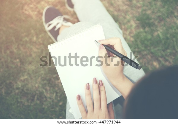 Female sitting in grass at the garden hold a pen and notebook