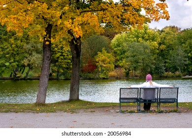 Female sitting on a bench in park (autumn)