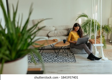 Female sitting on the floor in the living room and using laptop
