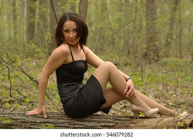 Female sitting on a log in the spring forest