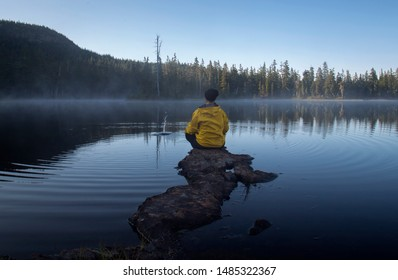 Female sitting on a rocky outcropping wearing a yellow jacket looking out over a rural lake in the early morning.
