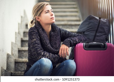 Female sitting on staircase next to suitcase and bag