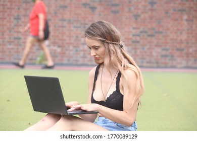 female sitting outdoors in the park working on a computer practicing socially distancing