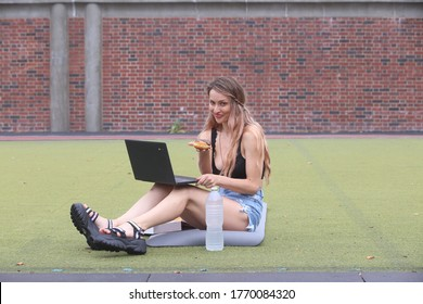 female sitting in the park working on a computer while holding a chocolate frosted doughnut