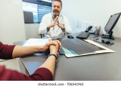 Female sitting at table in clinic with doctor in background. Focus on woman patient hands visiting doctor. Woman meeting with medical doctor to seek advice.