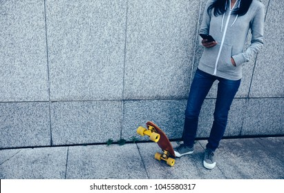 female skateboarder using smartphone leaning on wall in city