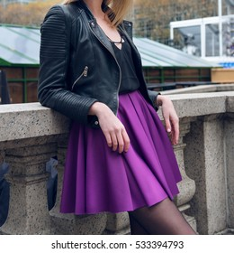 Female skater skirt and leather jacket. Girl wearing sexy fashionable outfit with black leather jacket and purple circle skirt. Model girl in fashion skirt.